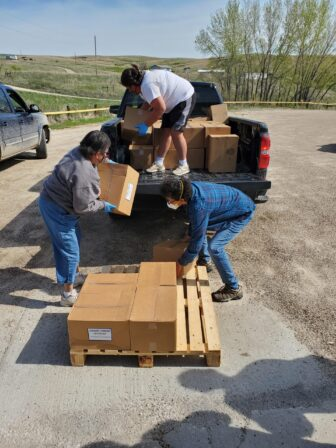 A team of volunteers loads boxes of food onto a pick-up truck to be distributed across Pine Ridge Indian Reservation.